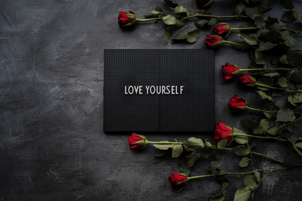 Roses and board reading Satya LOVE YOURSELF