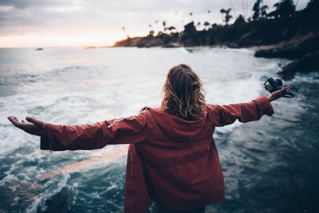 Woman embracing the ocean satya